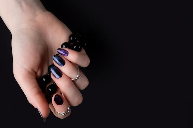 손톱에 어두운 반짝이 광택 디자인으로 아름 다운 손질 된 여자의 손