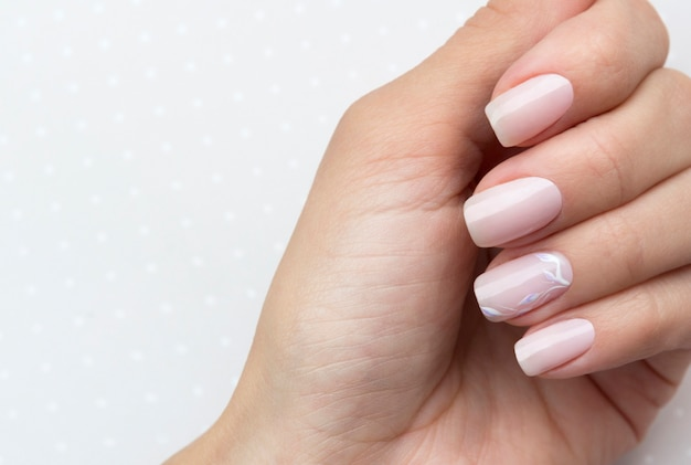Beautiful groomed woman's hands with feminine nails on the light gray table.