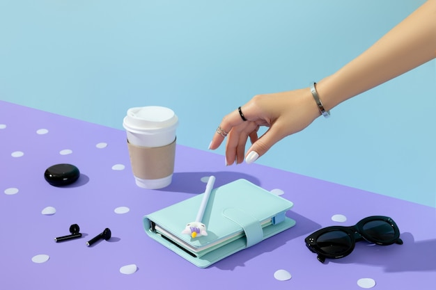 보라색 테이블 위에 아름 다운 손질 된 여자 손입니다. 여성 여름 액세서리.