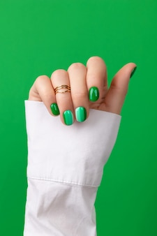 Beautiful groomed womans hand with green nails design on green surface