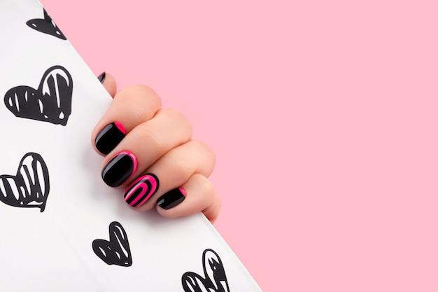 분홍색 유행 매니큐어와 아름 다운 손질 된 여자 손