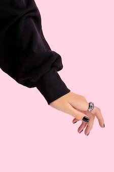 ピンクのトレンディなマニキュアで手入れの行き届いた美しい女性の手