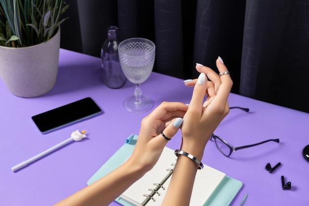 보라색 테이블 위에 아름 다운 손질 된 여자 손입니다. 여성 여름 액세서리