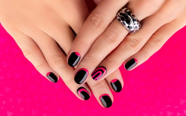 Beautiful groomed womans hands with trendy manicure on pink