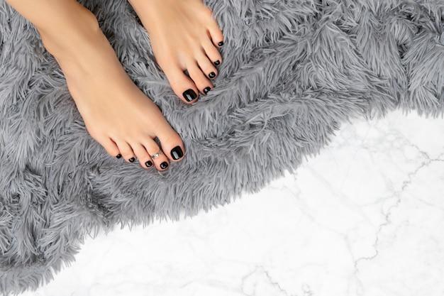 모피 표면에 검은 네일 디자인으로 아름다운 손질 된 여자 다리