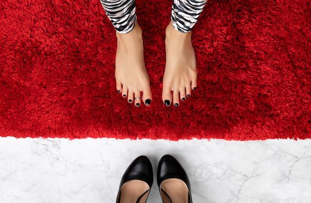 Красивые ухоженные женские ножки с черным дизайном ногтей на пушистой поверхности