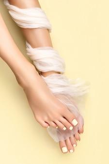 노란색 표면에 여름 네일 디자인으로 아름 다운 손질 된 여자 다리