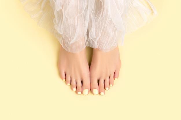 Красивые ухоженные женские ножки с летним дизайном ногтей на желтой поверхности