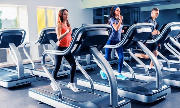 Красивая группа друзей, тренирующихся на беговой дорожке в ярком современном тренажерном зале