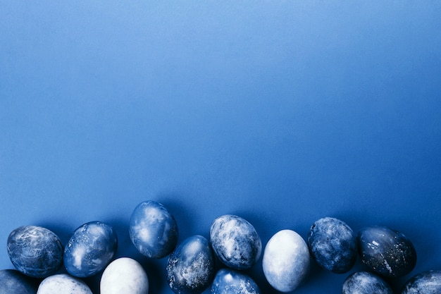 Beautiful group ombre blue easter eggs with quail eggs and feathers on a blue background