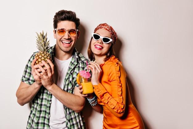 Bel ragazzo e ragazza in occhiali da sole e abiti estivi luminosi sorridono e si godono cocktail e ananas.