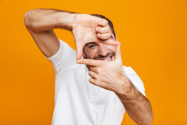 Красивый парень в футболке показывает рамку пальцами стоя, изолированный на желтом