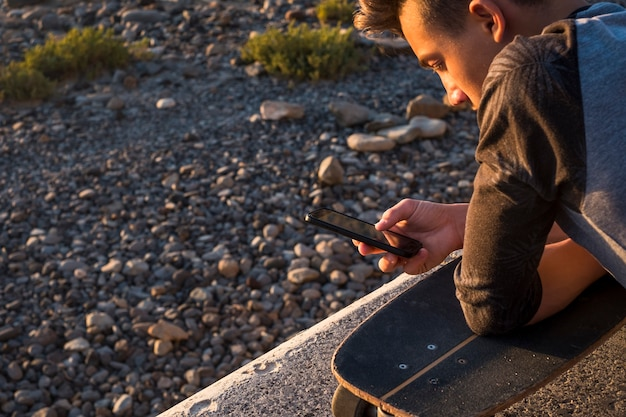 Beautiful guy and teenager at the beach alone with his phone - playing, chatting or viewing videos with his skateboard