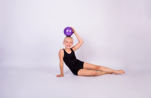 A beautiful gymnast girl in a black swimsuit with a ball sits on a white isolated wall with space for text