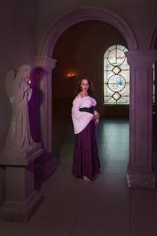 Крупным планом красивая цыганка в темной комнате соборной церкви с музыкальным бубном в руке