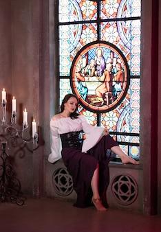 Крупным планом красивая цыганка в темной комнате соборной церкви с музыкальным бубном