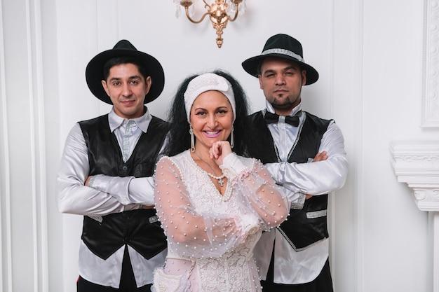 白いドレスを着た美しいジプシーの女性と明るい部屋に立っている2人の男