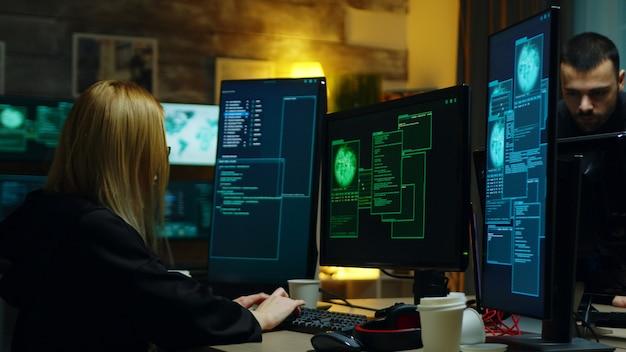 別の危険なサイバー犯罪者と一緒に働いている美しいハッカーの女の子。ハッカーセンター。