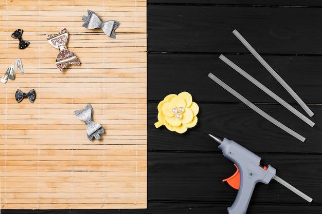 美しいヘアクリップと黒い木製のテーブルの上の熱い接着剤銃
