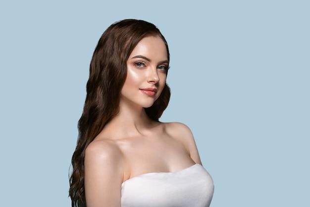 아름 다운 머리 피부 여자 초상화 자연 긴 곱슬 머리를 구성합니다. 색상 배경 파란색