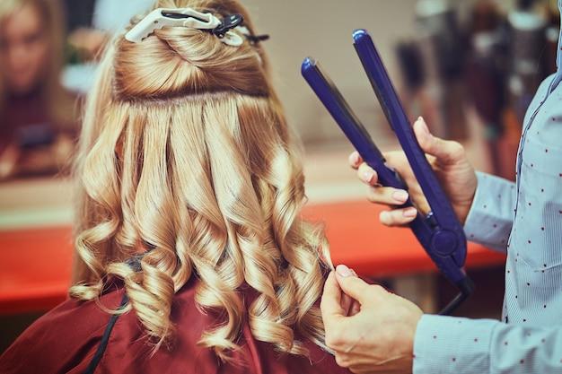 Красивая прическа молодой женщины после окрашивания волос и делая основные моменты в парикмахерской.