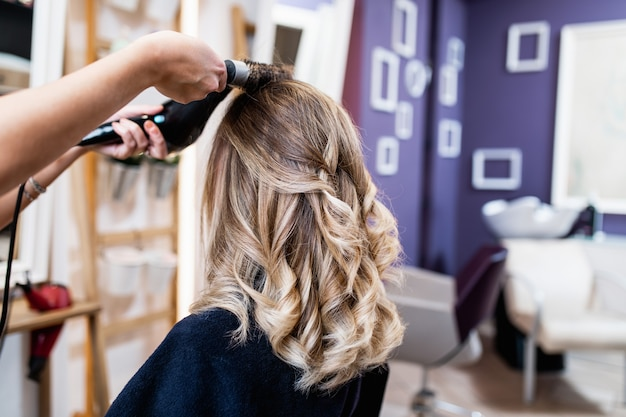 Beautiful hairstyle of young adult woman after dyeing hair and making highlights in hair salon.