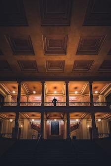 階段の上に立っている男性のシルエットの美しいホール