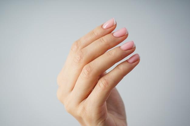 Красивая рука молодой девушки с красивым маникюром на сером фоне крупным планом. концепция спа и маникюра, французский маникюр.