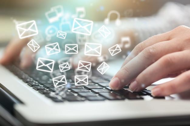 Красивая рука, работающая на ноутбуке с иконками электронной почты