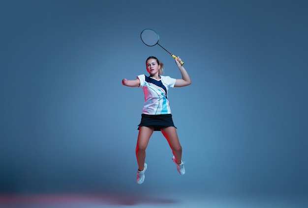 Beautiful handicap woman practicing in badminton isolated on blue background in neon light. lifestyle of inclusive people, diversity and equility. sport, activity and movement. copyspace for ad.