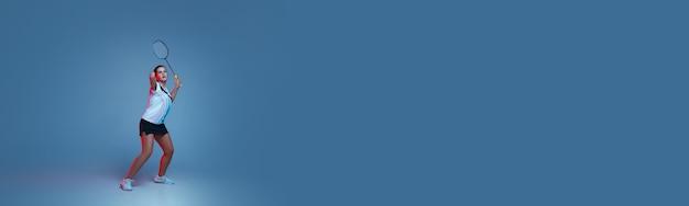 네온 불빛에 파란색 배경에 고립 배드민턴에서 연습하는 아름 다운 핸디캡 여자. 포용적인 사람, 다양성 및 평등의 라이프 스타일. 스포츠, 활동 및 움직임. 광고 copyspace입니다. 전단