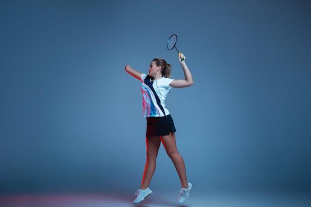 네온 불빛에 파란색 배경에 고립 배드민턴에서 연습하는 아름 다운 핸디캡 여자. 포용적인 사람, 다양성 및 평등의 라이프 스타일. 스포츠, 활동 및 움직임. 광고 copyspace입니다.