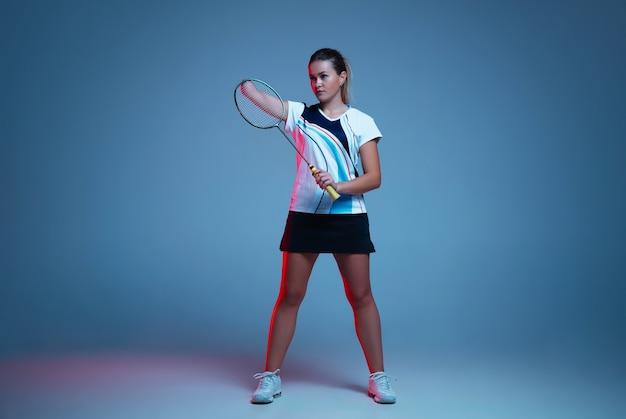네온 불빛에 파란색 배경에 고립 된 배드민턴에서 연습 하는 아름 다운 핸디캡 여자. 포용적인 사람들의 라이프스타일, 다양성과 평등. 스포츠, 활동 및 움직임. 광고에 대 한 copyspace입니다.