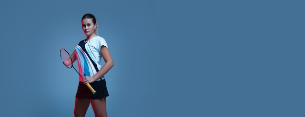 ネオンの光の青い背景で隔離バドミントンで練習している美しいハンディキャップの女性