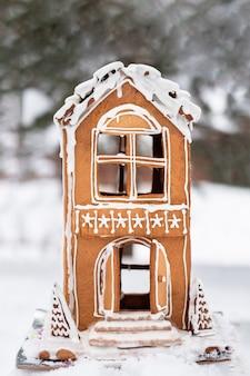 クリスマスと新年の雪と美しい手作りジンジャーブレッドハウス