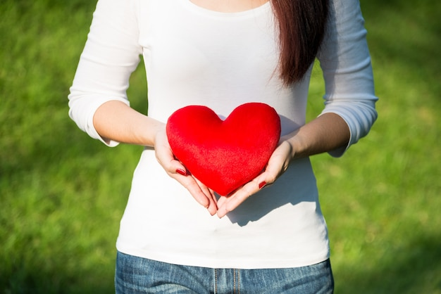Beautiful hands of asian woman holding red soft heart