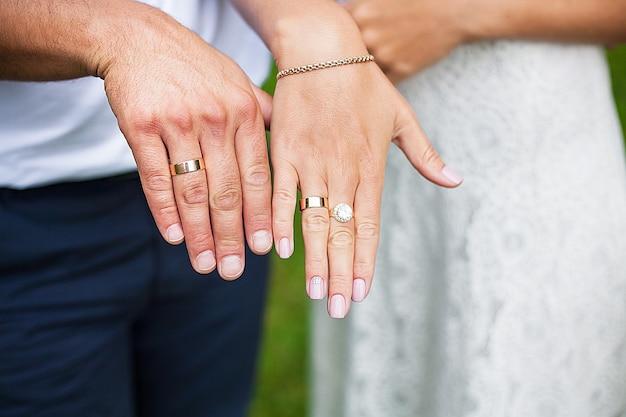 Красивые руки молодожены демонстрируют свои обручальные кольца