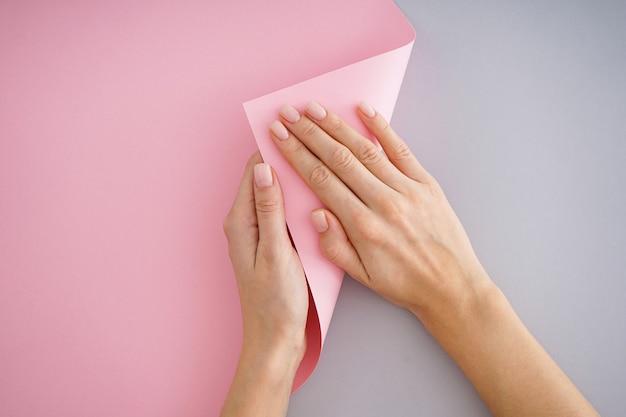 회색과 분홍색 배경에 아름다운 매니큐어와 어린 소녀의 아름다운 손, 평면 누워