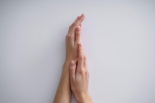 灰色の背景に美しいマニキュアを持つ少女の美しい手。フラットレイ。