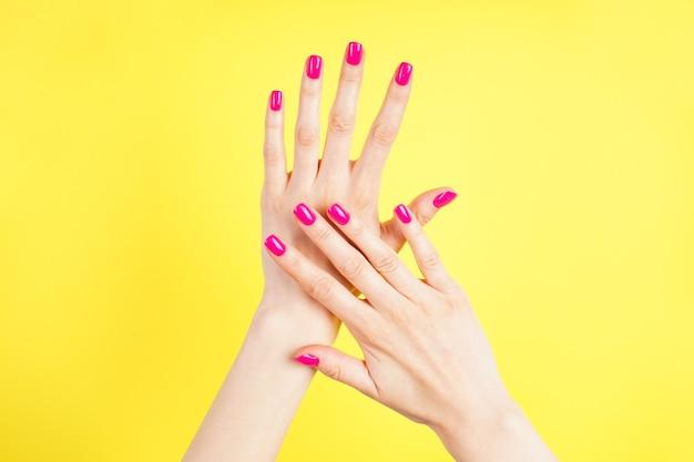 노란색 바탕에 젊은 여자의 아름 다운 손. 아름 다운 매니큐어 근접 상위 뷰입니다.