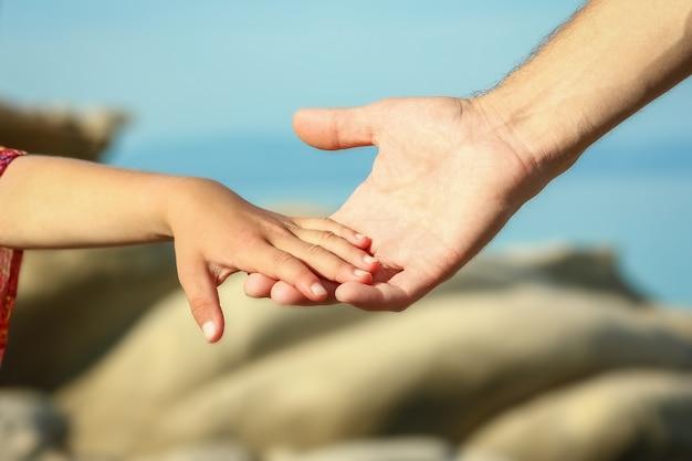 Красивые руки родителей и ребенка на берегу моря