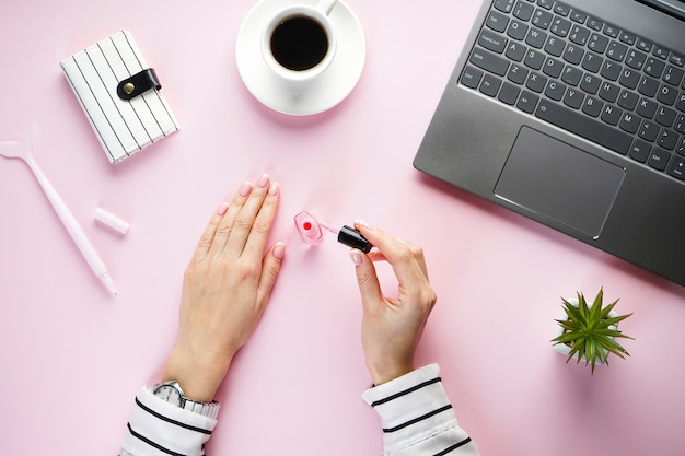 Beautiful hands of a young girl on a pink background with a laptop, a cup of coffee and a pink pen with a striped notebook. flat lay.