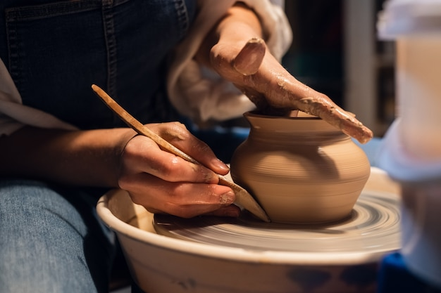 Beautiful hands of a young girl potter in the process of sculpting a vase with clay and tools.