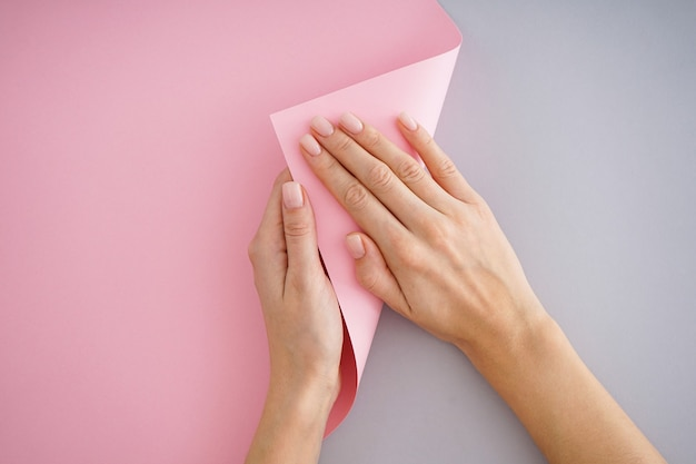Beautiful hands of a young girl with beautiful manicure on a gray and pink background, flat lay