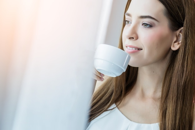 Beautiful happiness caucasian girl enjoy morning moment with hot coffee