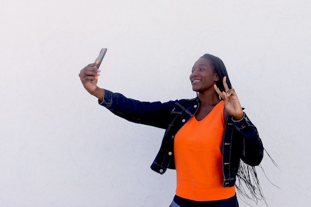 The beautiful and happy african american takes a selfie on a white wall