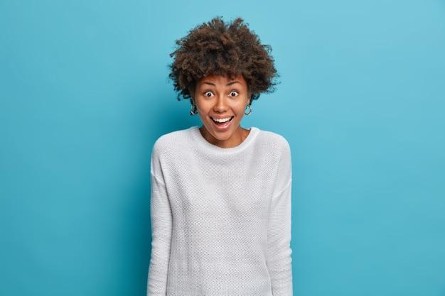 美しい幸せなアフリカ系アメリカ人の女性は、楽しい表情を驚かせ、突然の成功を信じることができず、カジュアルな白いジャンパーを着て、