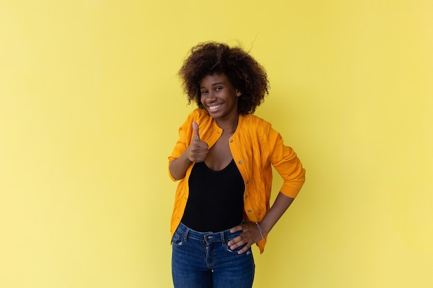 The beautiful and happy african american on a yellow background