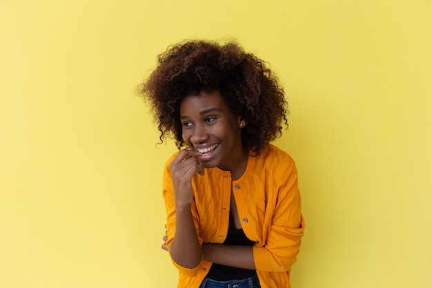 Beautiful and happy african american on a yellow background