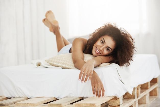 Bella donna africana felice che si trova sul letto a casa che sorride.